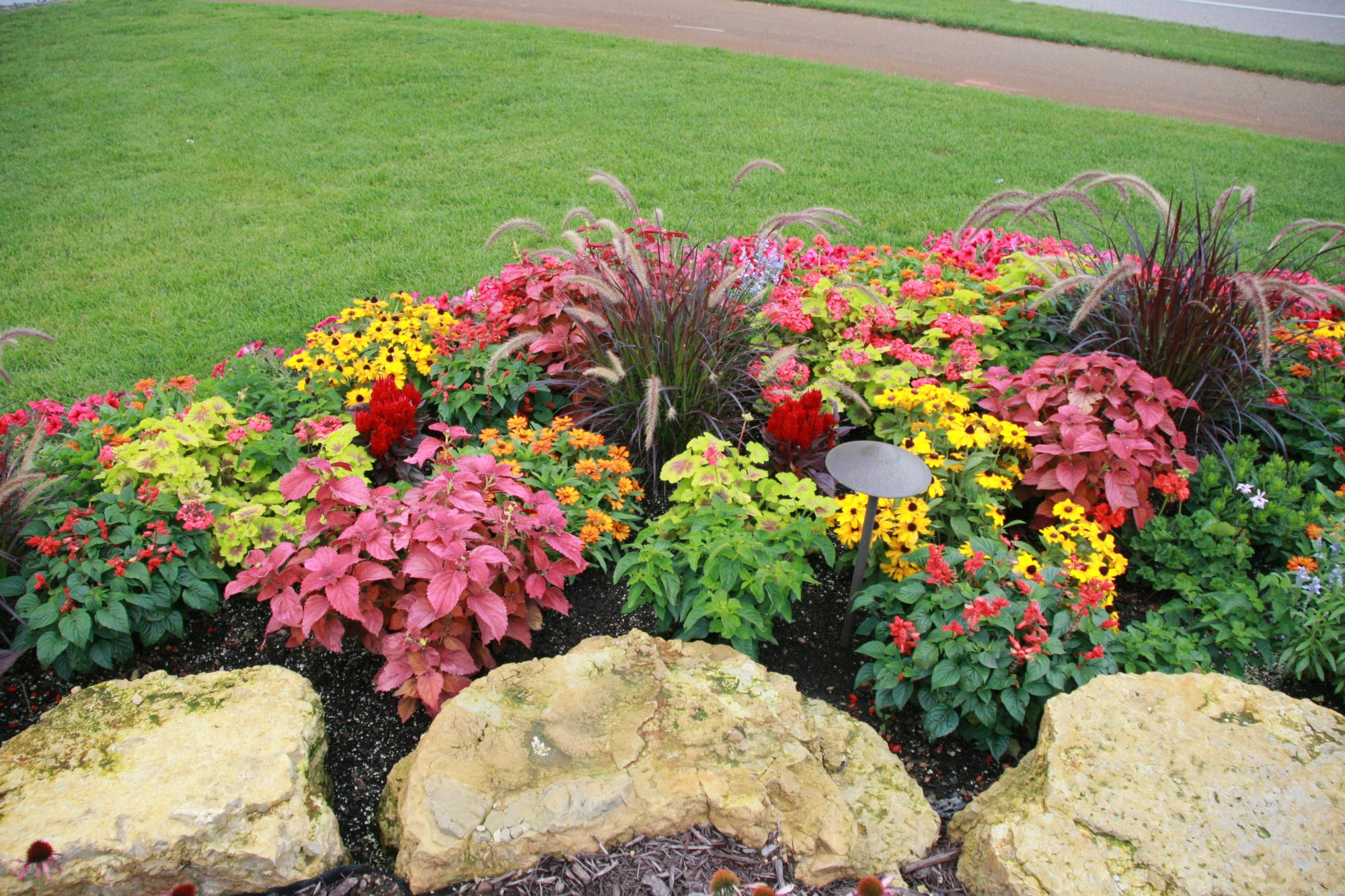 Outcropping stones and annual planting bed in lakeville for Flower landscape ideas